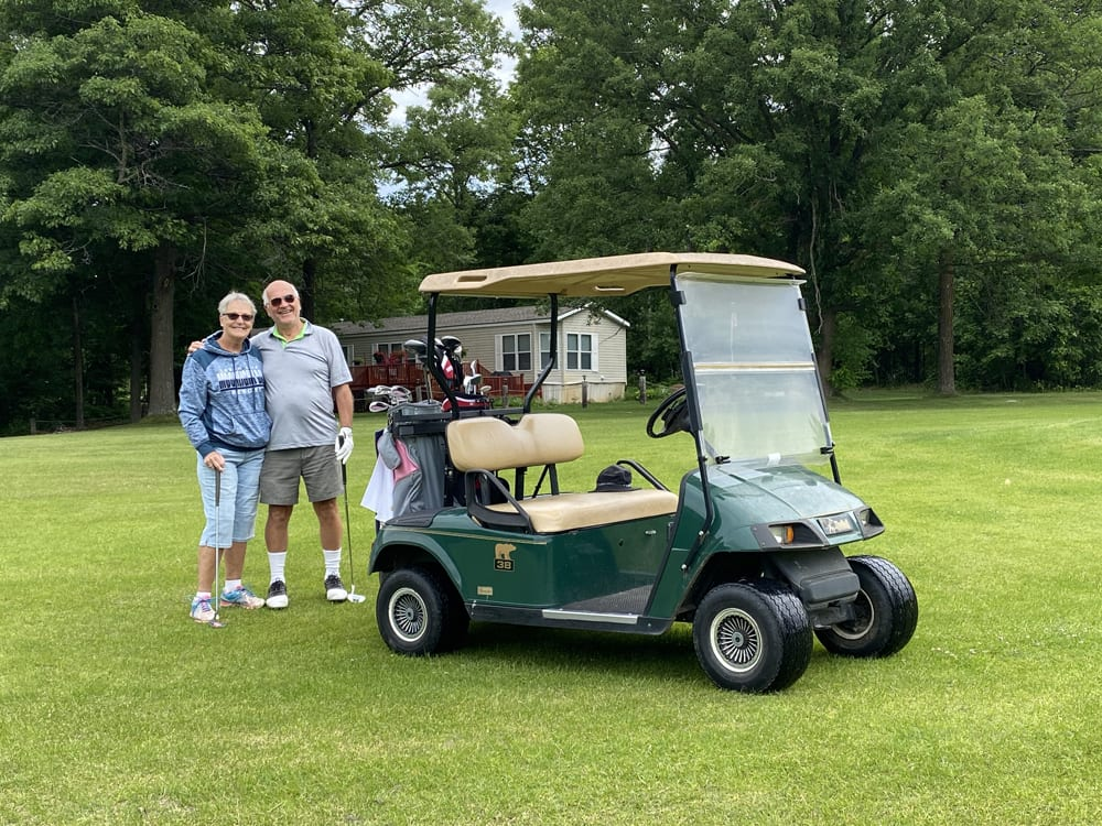 Couple on golf course with golf cart