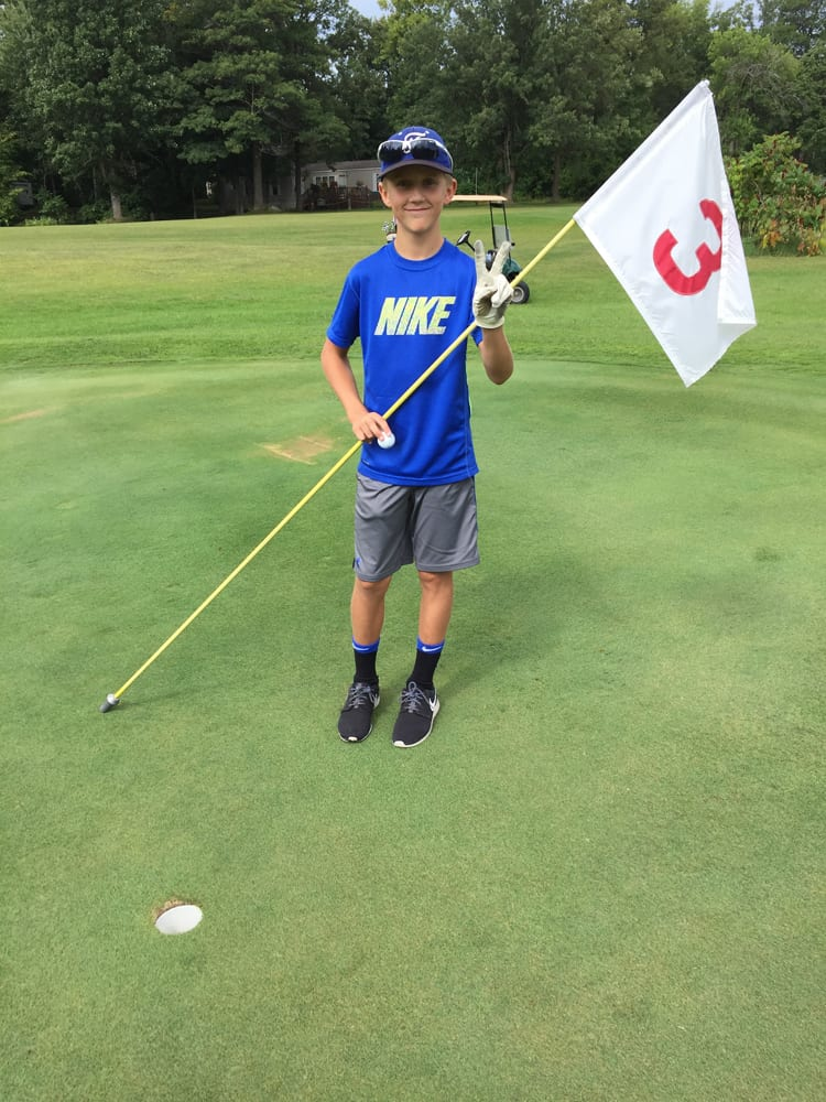 Young man holding hole 3 flag